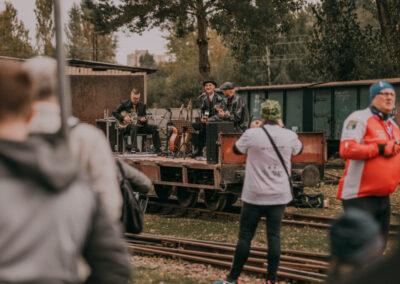 Zespól gra na platformie, mężczyzna robi im zdjęcie. Z prawej strony organizator rajdu w czerwonej koszulce.