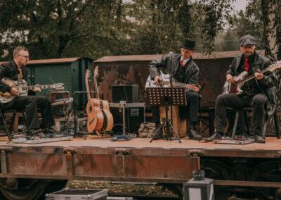 Trzech mężczyzn, członków zespołu Marka Makarona, grających na gitarach. Na scenie sprzęt muzyczny.