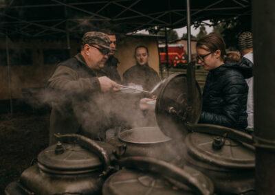 Mężczyzna w wojskowym ubraniu nalewa z kotła zupę.Dziewczyna podaje mu talerz. obok stoi drugi mężczyzna i młoda kobieta.
