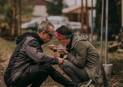 Kobieta i mężczyzna siedzą na torach i jedzą zupę z jednorazowych talerzyków. Mężczyzna trzyma w ręce kromki chleba.
