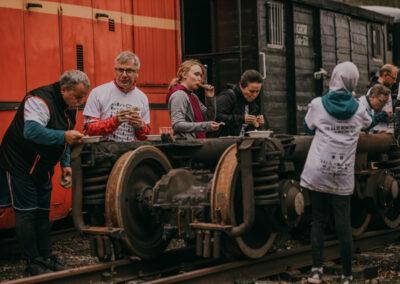 Ludzie stojący przy fragmentach starych wagonów i jedzący zupę z jednorazowych talerzyków.