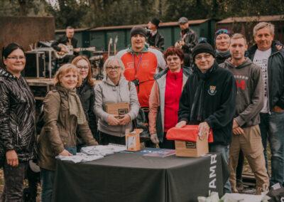 Ośmioro pracowników Centrum, dyrekor oraz pan Antonii Żurek stoja przy stole, na którym znajduje się urana z losami oraz koszulki rajdowe. W tle zespół wystepuje na scenie.