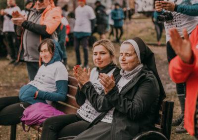 Trzy kobiety siedzące na ławce, jedna w habicie zakonnym klaszcze w dłonie, druga ubrana w koszulkę rajdową również klaszcze, trzecia w kapturze na głowie trzyma ręce w kieszeni.