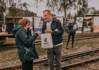 Zastepca Prezydenta Bytomia wręcza nagrodę w papierowej torbie kobiecie w ciemnej kurtce. Z tyłu dyrektor mówiący do mikrofonu. W tle banery sponsorów i partnerów.