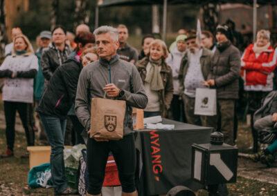 Wicestarosta tarnogórski z papierową torbą z logo powiatu tarnogórskiego. Za nim pracownicy rprzygotowujący nagrody i inni uczestnicy rajdu.
