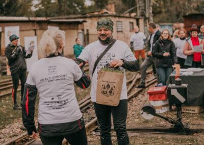Wójt gminy Świerklaniec wręczający nagrodę kobieciew koszulce rajdowej. W tle osoby rozdające nagrody.