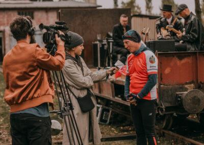 Dziennikarka z mikrofonem i mężczyzna z kamerą przeprowadzaja wywiad z dyrektorem Centrum, w tle platforma ze scena, na której gra zespół Marka Makarona.