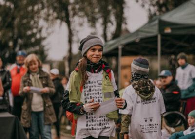 Usmiechnięta dziewczynka z kopertą z nagrodą. W tle inni uczestnicy rajdu i obsługa rajdu.