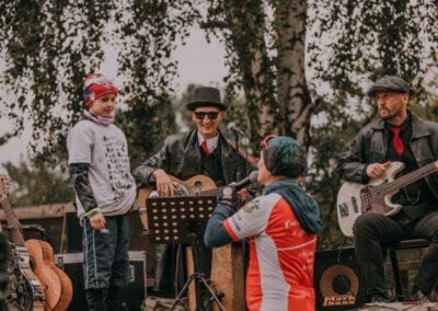Na scenie dwóch muzyków z gitarami oraz chłopiec w rajdowej koszulce. Pod scena dyrektor z mikrofonem mówi do chłopca.