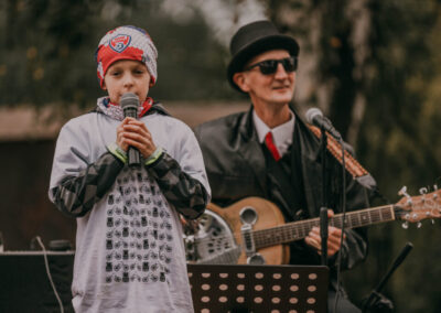 Chłopiec w rajdowej koszulce mówiący do mikrofonu. Za nim muzyk Marek Makaron w kapeluszu i ciemnych okularch z gitarą przewieszona przez ramię.