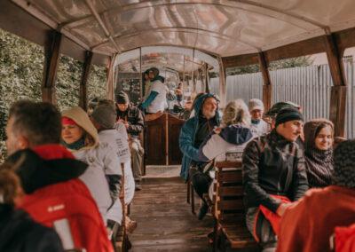 Uczestnicy rajdu siedzący wewnątrz wagonu kolejki patrzą przez okna. Z tyłu mężczyzna przechodzący między wagoonami.