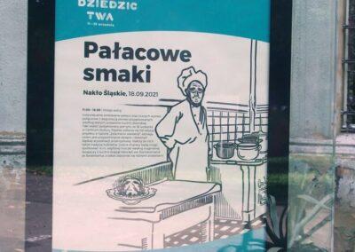 Plakat pałacowe smaki w szklanej gablocie przed budynkiem Centrum.