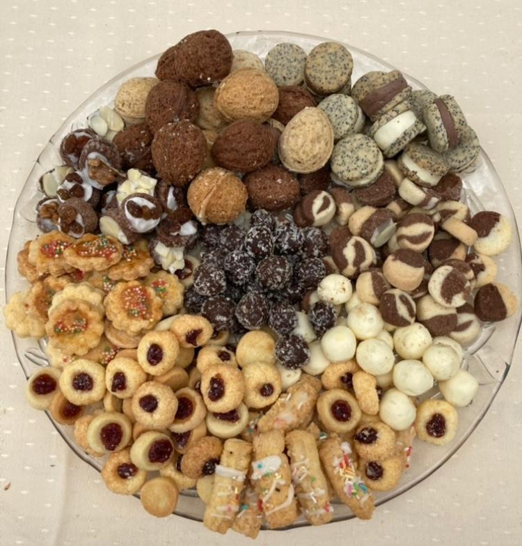 Szklany talerz, na którym ułożone są różne rodzaje kruchych ciasteczek.