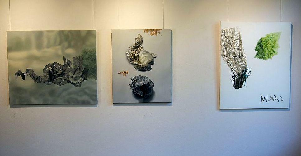 Trzy abstrakcyjne obrazy wiszące na ścianie.
