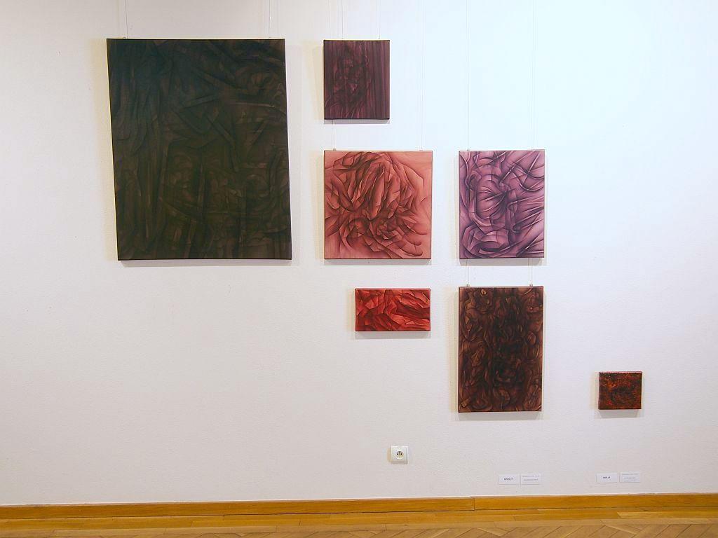 Siedem abstrakcyjnych obrazów w różnych rozmiarach wiszących na ścianie.