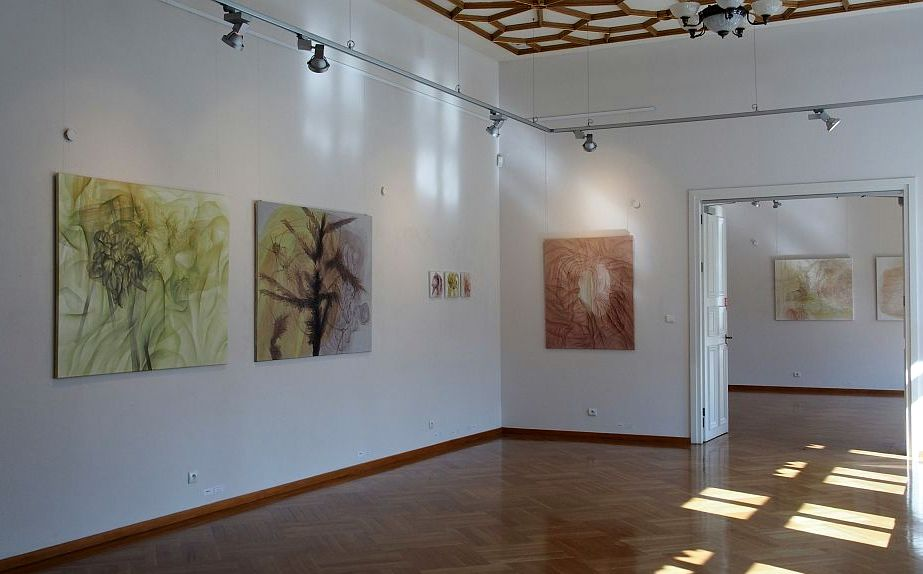 Sala z sufitem mozaikowym. Na ściamie z lewej strony dwa duże obrazy abstrakcyjne oraz trzy małe. Na scianie prostopadłej duży obraz abstrakcyjny. W tle otwarte drzwi do kolejnej sali i widoczne na ścianie dwa obrazy w jasnych kolorach.