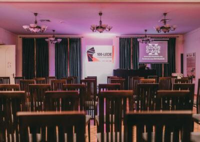 Pusta sala koncertowa, w tle logo 100-lecie powstań śląskich oraz ekran do projekcji z wyświetlona nazwą zespołu Sidor X S-Age.
