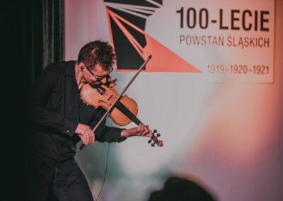 Marcin Sidor grający na skrzypcach, pochylony, w tle logo 100-lecia powstań sląskich.