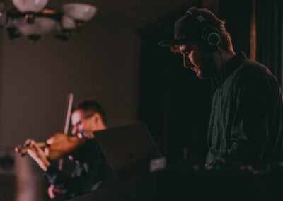 Na pierwszym planie z prawej strony Szymon Herbuś w słuchawkach przy konsoli. W tle Marcin Sidor grający na skrzypcach.