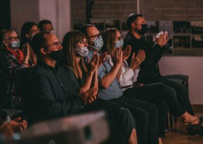 Grupa osób bijacych brawo i siedząca w pierwszym rzędzie na koncercie.