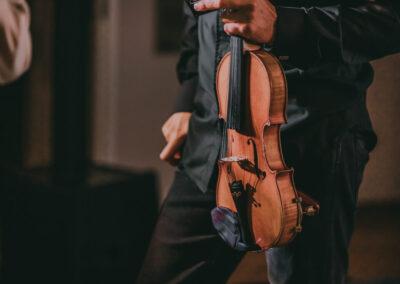Sylwetka mężczyzny od pasa w dół, trzymającego w ręce skrzypce.