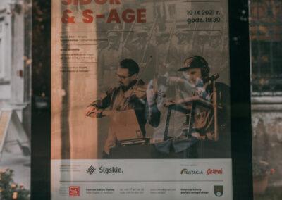 Plakat zapowiadający koncert z okazji zrulecia powstań sląskich Sidoe & S-Age w szklanej gablocie przed pałacem.