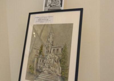 Obraz przedstawiający zabytek powiatu tarnogórskiego w ramie ustawiony na sztaludze. Nad nim stare zdjęcie.
