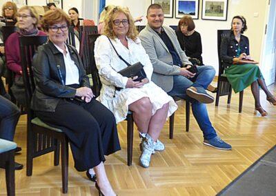 Beata hetmańczyk i sławomir Głaz z uczestnikami siedzą na na krzesłach w sali koncertowej.