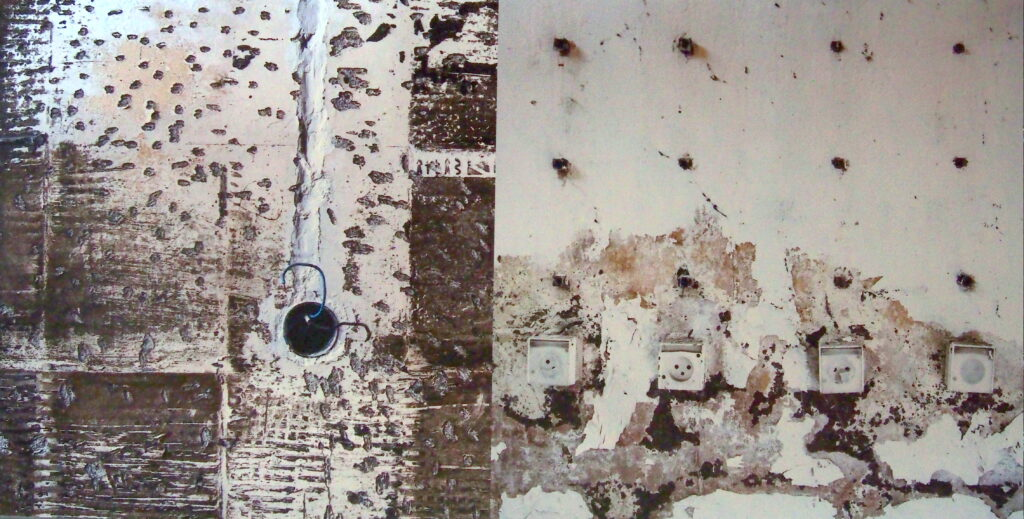 Obdrapana ściana z łuszczącą się farbą. Z lewej strony w scianie otwatra puszka elektryczna z wystającymi kablami. Po prawej na dole rząd gniazdek elektrycznych, nad nimi kikuty po uciętych, zardzewiałych drutach zbrojeniowych.