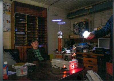 Wnętrze biura lub warsztatu. Przy biurku na środku siedzi mężczyzna. Na biurku urządzenie elektryczne z wystającymi do góry drutami emitującymi światło. Za mężczyzną wysoki regał. Z prawej strony pod ściana biurko, na którym stoi monitor komputera i mnóstwo pudełek.