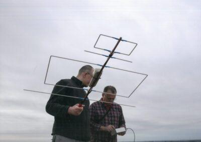Dwóch mężczyzn na tle szarobłękitnego nieba. Mężczyzna z lewej strony trzyma dużą anntene telewizyjną, mężczyzna z prawej strony trzyma w rękach małe urządzenie z kablem. Obaj patrzą na urządzenie.