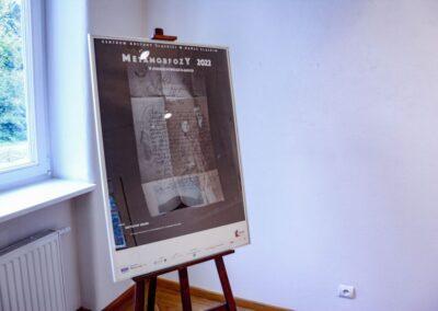 Plakat Metamorfozy 0222, czarne tło zdjęcie z kalenrarza - w ramie na sztaludze.
