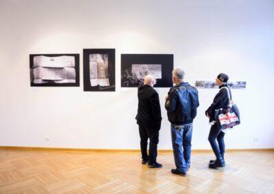 Trzy osoby stojące prze dściana ze zdjęciami z wystawy.