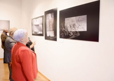 Kobieta w czerwonej marynarce przygląda się zdjęciom.