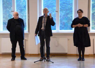 Dyrektor Centrum przy mikrofonie przemawia do gości, z lewej strony Krzysztof Miller, z prawej tłumaczka polskiego języka migowego.