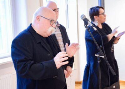 Krzysztof Miller przemawia do gości obok dyrektor i tłumacz.