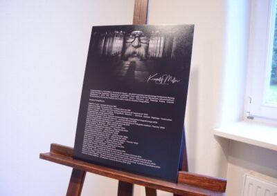 Czarna plansza ze zdjęciem Krzysztofa Millera i jego biogramem ustawiona na drewnianej sztaludze.