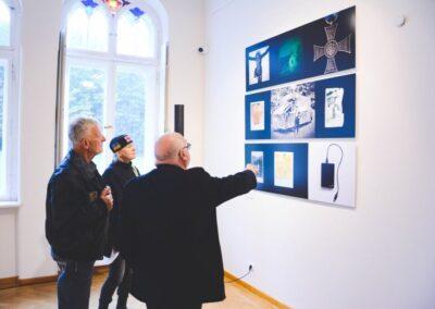 Autor wystawy wskazujący zdjęcia na scianie dwóm osobom ogladającym wystawę.
