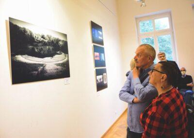 Kobieta w kraciastej koszuli i mężczyzna drapiący się po brodzie z zainteresowanie przyglądaja się zdjęciu z wystawy.