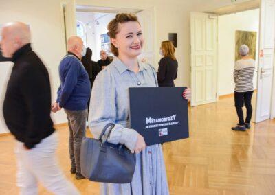 Usmiechnieta prezes Stowarzyszenia Góry Kultury trzymająca w dłoniach czarną teke kolekcjonerską z napisem Metamorfozy 2022 i logiem 100-lecie powstań sląskich.